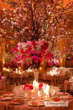 A grand wedding centerpiece of orchids and romantic cherry blossoms serves as a focal point for this elegant indoor wedding.