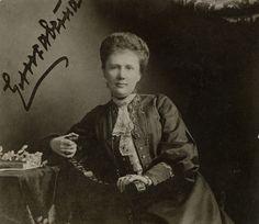 Grã-duquesa Elisabeth Mavrikievna em 1905. Ela está sentada em uma cadeira de madeira, com ambas as mãos descansando no braço direito. Ela está usando um terno escuro com uma camisa de laço e um longo colar. Há flores e um livro sobre uma mesa ao lado dela para a esquerda. A fotografia é assinada no canto superior esquerdo. Grã-duquesa Elisabeth Mavrikievna, nascida princesa Elisabeth de Saxe-Altenburg, era a consorte de Grão-Duque Constantino Constantinovich.