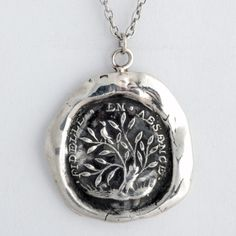 Pyrrha's Fidelity Talisman Necklace. In French, this handcrafted wax seal necklace reads Fidele En Absence which means Fidelity in Absence. Pictured is a turtle dove perched on the tree of life, a symbol of interconnectedness and unity.