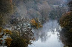 Mist rises from the River Avon viewed from the Dundas Aqueduct as the sun rises near Bath in south western England