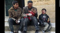 A man holds a baby who was rescued from rubble after an airstrike in Aleppo on February 14, 2014.