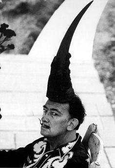 """Port Lligat, octobre 1959. Dali, coiffé d'une corne de rhinocéros, avec les fameuses graines volantes de pissenlit """"je sème à tout vent"""" fixées à la pointe de ses moustaches. Photo: Robert Descharnes www.daliphoto.com"""