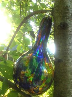 "This is an absolutely beautiful hand blown witch ball/sun catcher with hues of cobalt blue, orange, green and yellow. Reminds me of colors you would see in a peacock. Would be perfect in the kitchen window, hanging from a front porch or for any home. It is aprox. 8"" tall and 4 1/2"" wide and shaped like a teardrop. $30.00"