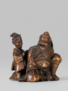 A Hida school boxwood okimono type netsuke of Shôki and oni, by Shôko. Late 19th century Seated and enjoying the massage that an oni dressed as a woman is giving him by beating his shoulder with its fists. The eye pupils of black glass. Signed Shôko.