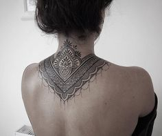 Ornamental style tattoo covering back of the neck and upper back.Done by Alex Bawn