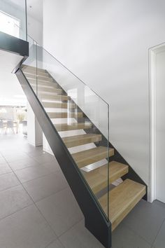 These stairs in a home in England feature wooden treads with a glass safety rail.