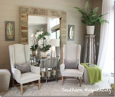 Love this huge mirror leaning against the wall with two chairs and a table grouped in front of it.