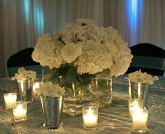 Low centerpiece surrounded by single blooms and candles