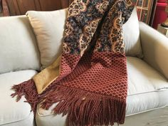 Unique among the unique, this handmade throw blanket features three chenille tapestry fabrics...in the center of side one is a luxurious Moroccan design in black navy, terracota, beige/gold tribal pattern. Surrounding this distinctive attraction are borders of terracota and gold diagonal chenille. The third fabric--a gold chenille--is the back of the two amazing patterns, and the throw is finished with a terracota/gold fringe that adds the grand finale!!! All three fabrics are compr...