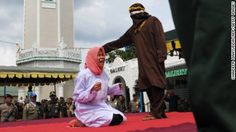 An unrelated man and woman who had been seen alone together were caned in public in Banda Aceh, Indonesia, for violating Sharia law, a police chief said.