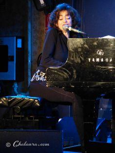 Foto lateral de Carmen París mientras toca su piano y canta mirando hacia el público