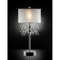 This Crystal Shireen Table Lamp is a modern take on mid-century style. The lamp boasts a hip retro feel with the fabric shade and dripping crystals from the center.