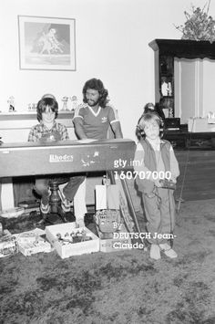 Barry and his children in front of a Rhodes electric piano.