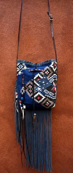 Ooo So Santa Fe  All of my bags are made by hand and each is one-of-a-kind, incorporating a combination of retired vintage Navajo blankets / rugs, vintage or gently-used horse tack, and deer, elk or cowhide leathers. I embellish the bags with vintage trade beads, turquoise, coral, nickel silver/German silver Concho buttons, nickel silver spots/studs, and deer antler tips. Pillow ticking or unbleached muslin is used for the linings, and all the fringe is hand-cut. www.ooososantafe.com