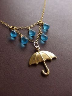 "How could you not love this necklace? It's a simple, but amazing design. I'm not usually a fan of gold-tone, but I love the necklace so much. The umbrella charm with the blue ""droplet"" beads. So cute."