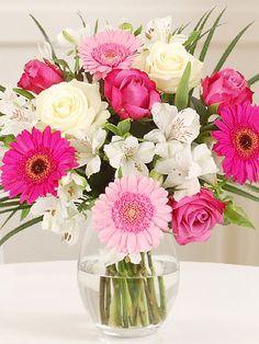Josette: Alegre combinación de rosas, gerberas y astromelias en tonos rosas y blanco acompañadas de follaje en florero de vidrio.