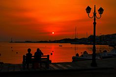 Couple sitting on a bench and watching the sunset on Tinos town waterfront. Shadow Silhouette, Best Honeymoon, View Image, Dream Vacations, Cool Photos, Greece, Places To Go, Sunrise, Island