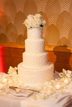 White 4-tier wedding cake with floral topper | Roy Llera Photography | Cake: Four Seasons Hotel