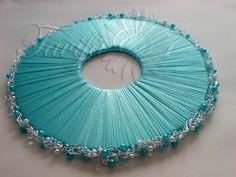 Диск каркас для букета невесты. Вырезан из коматекса толщиной 4мм,д иаметр - 18 см, обмотан тоненькой тесемочкой  шириной 3мм. По кругу крючком связано обрамление из тоненькой серебристой проволоки   в которое вплетены  мелкий жемчужно белый биссер,  рубленный стеклярус перламутровобелого цвета и светлоголубого цвета, дополнено белыми и бирюзовыми жемчужинами разного размера и  прозрачными бесцветными стеклянными бусинами, к