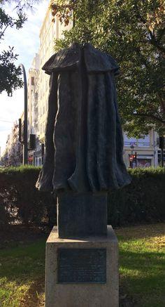 "This headless figure in a cape has a plaque that reads ""A La Capa Española"" and is located in the Gardens of La Glorieta. It was created by the sculptor Carlos Verdu and donated by the Asociación Valenciana de Caballeros de la Capa Española to the city of Valencia."