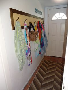Paint, coat hooks, and stained baseboards turn the plain, chalky white wall in the laundry room into a pool towel space.