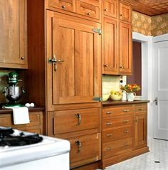 The refrigerator is a modern built-in model with freezer drawers on the bottom, but it's covered with cabinetry-matching wood panels to evoke the look of an old-fashioned icebox.  Hefty door handles and hinges enhance the effect.