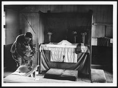 Padre decorating the altar in makeshift Church on the Western Front, WW1. People's Collection Wales.