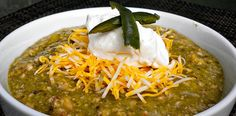 Denver Green Chili: 1 roasted chicken or 1 pound uncooked boneless pork chops cubed,  1T olive oil,  1 onion chopped,  2  tsp cumin, s to taste, 1c peeled, roasted and chopped green chiles (6-8 medium chiles)  3 cloves garlic minced,  3 T flour, Up to 4 cups chicken stock,  3-5   tomatillos, blanched and pureed, 2    teaspoons oregano