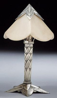 Albert Cheuret (1884-1966) Lampe «Palmier» Précieuse lampe en bronze à patine argent. Fût formé de feuilles imbriquées. Coiffe lumineuse à quatre plaques d'albâtre triangulaires à bords arrondis, chapeautée de feuilles éffilées. Piètement étoilé formé de feuilles superposées. Signature incisée «Albert Cheuret» sur une feuille du fût. H: 41 cm Lumière D: 23 cm