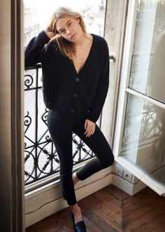 Black v neck cardigan, black skinny jeans, black shoes: Camille Rowe