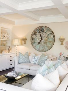 Sick of thinking about Winter weather? Now is a great time to get a head start on updating your beach home! A beautiful wooden clock, soft blue pillows, coral and shell accessories, and a distressed floor lamp complete the cozy room in the first photo, while the second photo brings together unique items like the light fixtures, large green Bordeaux bottles, and a small piece of driftwood to create an amazing dining table display.
