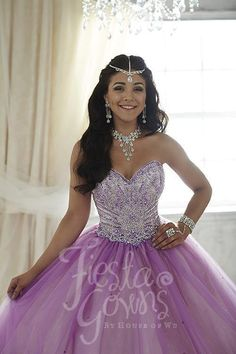 This full tulle ball gown has iridescent sequins speckled lightly on the skirt. Colorful rhinestones merge with sequins in a wonderful display on the bodice, completing this sweetheart neckline dress.