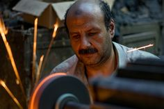 """Cairo Craftsman - A craftsman polishes a piece of metal in his small shop in Cairo Egypt. This is part of a personal project entitled """"Working"""" that celebrates the wide range of work done by people around the world. You can see it at http://ift.tt/2l4KykU"""