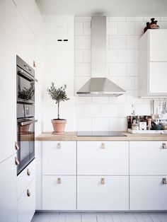 Minimalistic and bright kitchen with white cabinets and leather handles.
