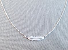 "Brushed Silver Small Feather Necklace. Check out this super cool feather sterling silver necklace. Necklace looks lovely on it's own but can be layered with your favorite pieces for a ultra-stylish look. Necklace measures 16"" long and features a lobster clasp closure with 2"" extension. Feather measures .75"" long."