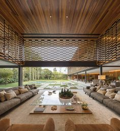 Lounge area partially shielded from the sun by a perforated wood paneling which still allows for airflow in this home located in Sao Paulo, Brazil. [2000 × 2190] : RoomPorn