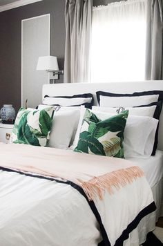 Master bedroom bed linens, black and white with green throw pillows.