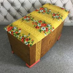 This early plywood blanket box has a beautiful curved front with a naturally bold grain. The lid is newly upholstered in a vintage French printed cotton. The decorative motif continues down the front of the box in a hand painted embellishment. To finish the feet are painted a glossy coral matching the roses of the upholstery.