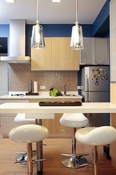 Due to space constraints, the kitchen and dining areas were merged, with the white versatile countertop moonlighting as the dining table and kitchen prep counter. It%u2019s surrounded by modern barstools that function as informal dining chairs.