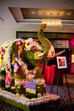 Wedding guests were welcomed to the cocktail hour by an elephant constructed of green moss, colorful mums, carnations, and orchids. #IndianWedding #elephant #topiary Photography: Davina + Daniel. Read More: http://www.insideweddings.com/weddings/vibrantly-colored-indian-wedding-in-new-orleans-lousiana/579/
