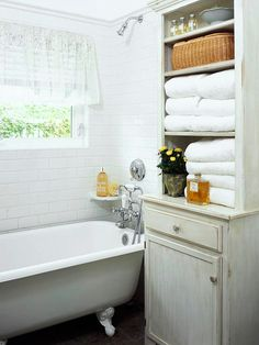 An antique hutch serves as bathroom storage. The open shelves hold towels while the door below conceals toiletries. The wood is protected from splashes by a marine-quality clear varnish.