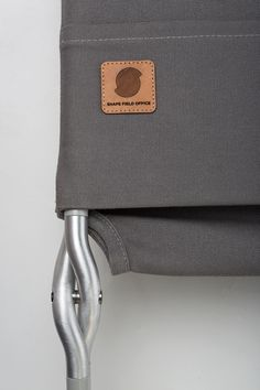 Lightweight aluminum folding chair with a waxed canvas sling. The hinge is made from two of the same part.