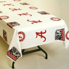 """Alabama Plastic Tablecloth by Rico. $5.95. These heavy duty plastic table covers are perfect for game day parties or tailgating. They are officially licensed and feature your team?s logos. The table cover is 54""""x108"""" and fits a standard 8ft. banquet table or 2 card tables if cut in half."""