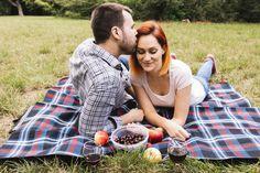 Hombre besando a su novia tendida en una manta sobre hierba verde con frutas Foto gratis