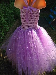 👸Rapunzel from Tangled inspired tutu dress made with a lilac crochet top, purple glitter fabric with diamonte mesh on the front, double satin ribbon straps and bow, lilac plain and sequin tulle and chiffon flowers. Comes with matching bow or flower on a hair clip💖 This is a double layer tutu and is long (ankle length) Safety Testing: This material conforms to EN71-2 (flammability) and EN71-3 (migration of certain elements). Matching blinged pumps are available to order at a discount when…