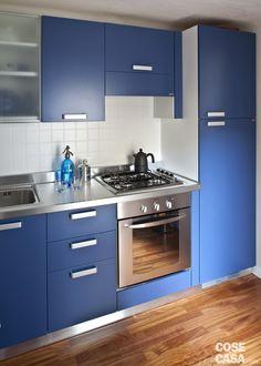 piastrelle in vetro e acciaio cucina : la cucina ha finitura blu laccato opaco, con top e maniglie in acciaio ...
