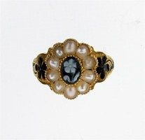 A Victorian memorial ring. Centred with a carved forget-me-not cameo and pearl surround, with further black enamel decoration to the shoulders and shank