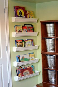 Rain Gutter book shelves behind a door. Galvanized Paint Buckets for everything else . . . indestructible!!!