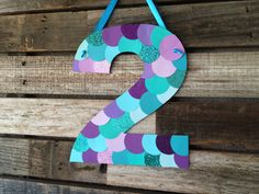 Hang this adorable Mermaid Inspired Party Number sign at your next party! Made to look like fish scales! Use it as a door sign or hang it at a gifts table! ***Sand Dollars are not included- please see shop for separate listing** Colors: Shades of purple, blues, and teal with some glitter. Size: Approx. 9wide by 11 tall. Each number will vary in size due to the shape of the number, for example, the number 1 will not be as wide as this number 5 shown above. It will still be at least 11 tall…