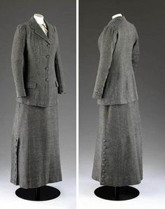Walking suit, Redfern, London, ca. 1911. Woollen tweed coat & skirt with silk lining. Black & white diagonally ribbed hip-length coat with button fastening, and ankle-length skirt. Diagonally striped tweed with stripes laid out in different directions to create visual interest. Cuffs & skirt bordered with deliberately mis-aligned bands of same fabric. Decorative buttons down skirt's side seam. Victoria & Albert Museum